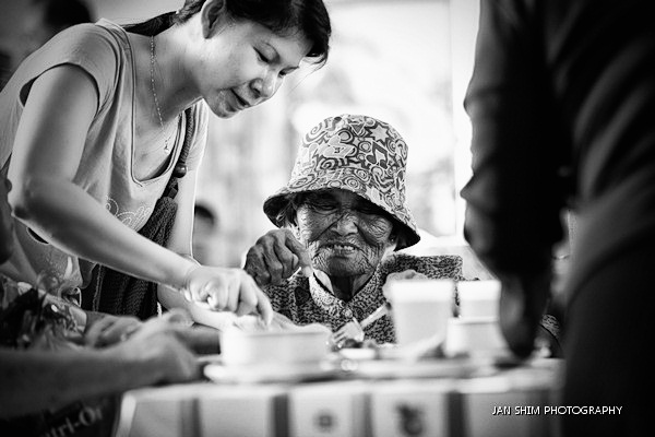 A student helps an elderly resident with her meal while keeping her company